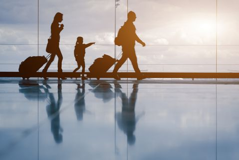 Silhouette of young family with luggage walking at airport